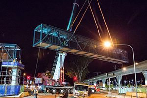 An 80-metre-long pedestrian bridge has been lifted onto place as part of the $8.3 billion Sydney Metro Northwest project in a precision night-time operation.